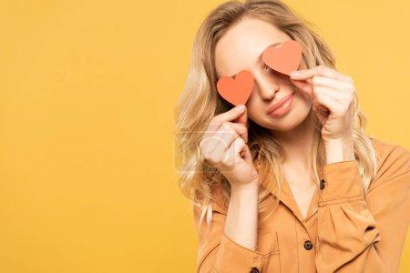Photo pour Femme souriante couvrant les yeux de signes cardiaques en papier isolés sur jaune - image libre de droit