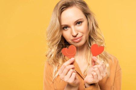 Foto de Smiling blonde woman holding paper hearts isolated on yellow - Imagen libre de derechos