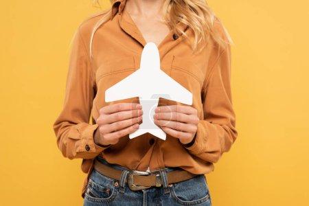 Photo pour Vue recadrée d'une femme tenant un avion en papier isolé sur jaune - image libre de droit