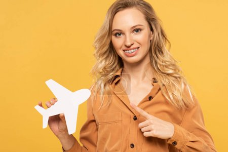 Photo for Smiling blonde woman pointing on paper plane isolated on yellow - Royalty Free Image