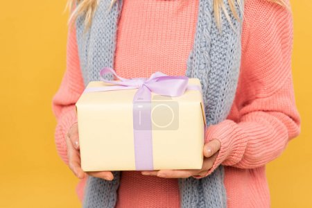 Cropped view of woman on sweater holding gift box isolated on yellow