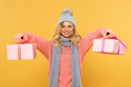 Photo for Smiling blonde woman in hat and scarf holding gift boxes isolated on yellow - Royalty Free Image