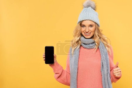 Photo for Smiling woman in hat holding smartphone with blank and showing approval sign isolated on yellow - Royalty Free Image