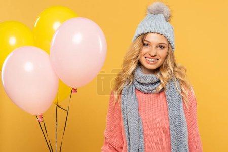 Photo pour Femme en chapeau et écharpe souriant et tenant des ballons isolés sur jaune - image libre de droit