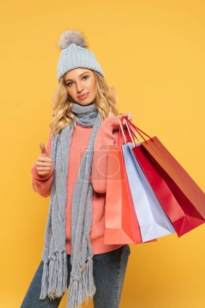 Photo for Woman in hat and scarf holding shopping bags and showing thumb up sign isolated on yellow - Royalty Free Image