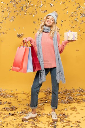 Photo for Smiling woman in hat holding gift box and shopping bags while falling golden confetti isolated on yellow - Royalty Free Image