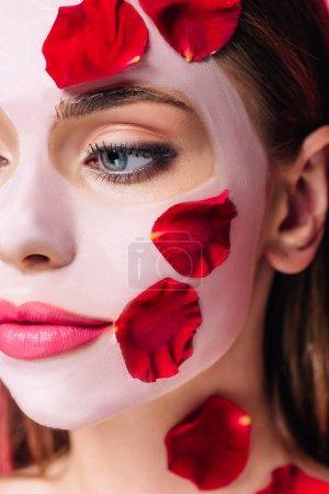 Photo pour Vue de près d'une belle femme en masque facial avec des pétales de rose - image libre de droit