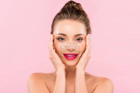 Photo pour Belle femme nue aux lèvres roses posant avec la main sur le visage isolée sur le rose - image libre de droit