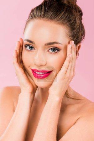 Photo pour Belle femme nue souriante aux lèvres roses posant avec les mains sur le visage isolé sur le rose - image libre de droit