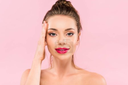 naked beautiful woman with pink lips posing with hand on face isolated on pink