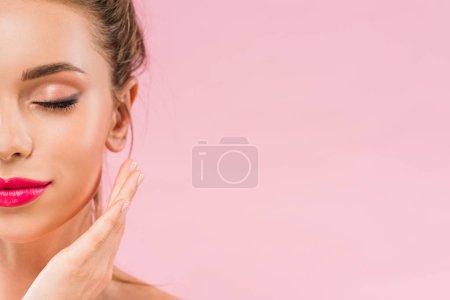 Photo pour Vue recadrée de belle femme nue avec des lèvres roses posant avec la main près du visage et les yeux fermés isolés sur rose - image libre de droit