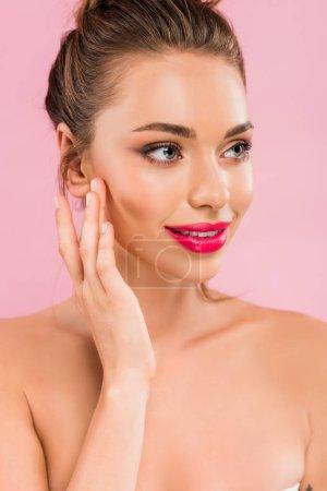 Photo pour Belle femme nue souriante aux lèvres roses posant avec la main près du visage et regardant loin isolée sur rose - image libre de droit