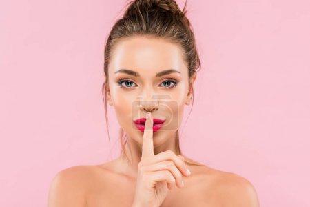 Photo pour Belle femme nue aux lèvres roses montrant un geste shh isolée sur rose - image libre de droit