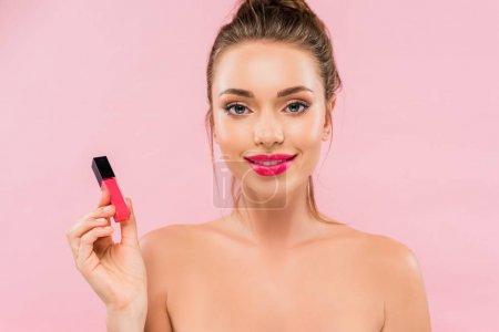 Photo pour Belle femme nue souriante aux lèvres roses tenant le brillant des lèvres isolé sur le rose - image libre de droit