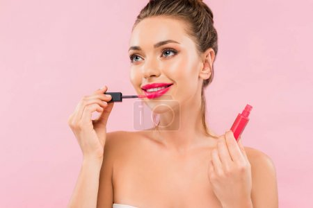 Photo for Smiling naked beautiful woman with pink lips applying lip gloss isolated on pink - Royalty Free Image