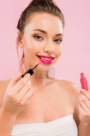 Photo pour Jolie femme souriante aux lèvres roses appliquant un lustre sur les lèvres isolée sur le rose - image libre de droit