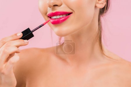 Photo for Cropped view of smiling naked beautiful woman with pink lips applying lip gloss isolated on pink - Royalty Free Image