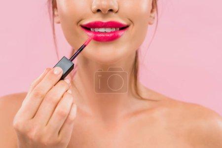 Photo pour Vue partielle d'une belle femme nue souriante aux lèvres roses appliquant un lustre sur les lèvres isolée sur le rose - image libre de droit