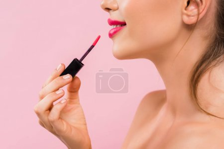 Photo pour Vue croisée d'une belle femme nue souriante aux lèvres roses appliquant un lustre sur les lèvres isolée sur le rose - image libre de droit
