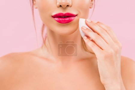 Photo pour Cropped view of naked beautiful woman with pink lips holding makeup sponge isolated on pink - image libre de droit