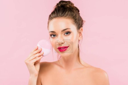 Photo for Naked beautiful woman with pink lips holding facial cleansing brush isolated on pink - Royalty Free Image