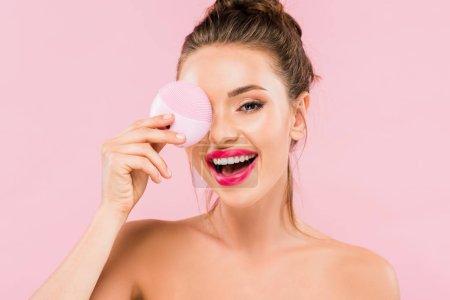 Photo pour Happy naked belle femme aux lèvres roses tenant le nettoyage facial brosse isolée sur rose - image libre de droit