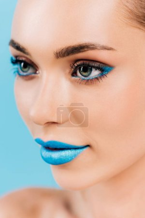 Photo for Close up view of beautiful woman with blue makeup isolated on blue - Royalty Free Image