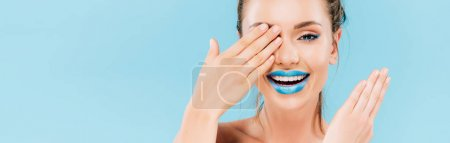 Photo for Happy beautiful woman with blue lips covering eye with hand isolated on blue, panoramic shot - Royalty Free Image