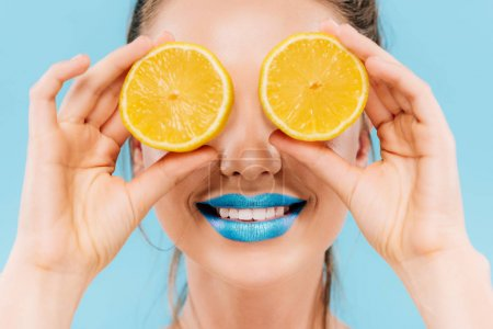 Photo for Smiling beautiful woman with blue lips holding orange halves on eyes isolated on blue - Royalty Free Image