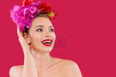 excited naked beautiful woman with red lips and floral wreath on head looking away isolated on crimson