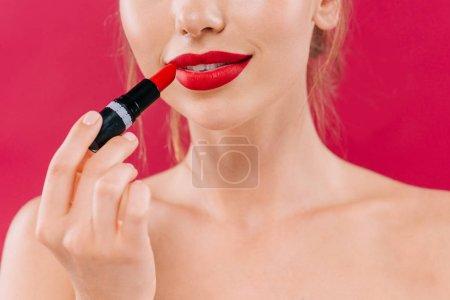 Photo pour Crochet vue d'une belle femme nue aux lèvres rouges appliquant un rouge à lèvres isolée sur cramoisi - image libre de droit