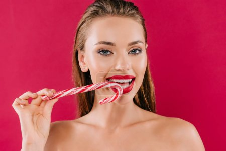 Photo for Naked beautiful woman with red lips eating sweet striped candy isolated on burgundy - Royalty Free Image