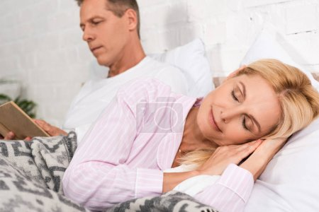 Photo pour Concentration sélective de la femme qui dort au lit alors que son mari lit un livre - image libre de droit
