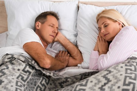 Photo for Mature couple sleeping in bed together - Royalty Free Image