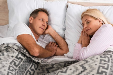 Photo for Man looking at sleeping wife in bed - Royalty Free Image
