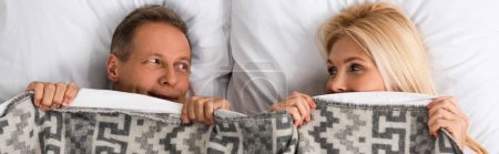 Photo for Panoramic shot of mature couple covering with blanket and looking at each other - Royalty Free Image