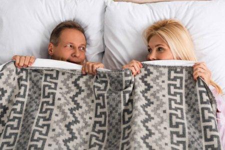 Photo pour Vue de dessus du couple couvrant avec couverture et se regardant - image libre de droit