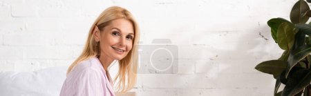 Photo pour Photo panoramique d'une femme souriante regardant une caméra à la maison - image libre de droit