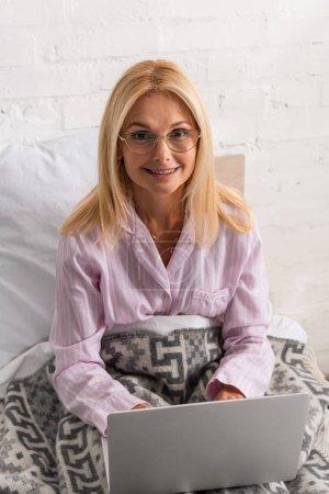 Photo pour Femme souriante dans un pyjama souriant à la caméra alors qu'elle utilise un ordinateur portable au lit - image libre de droit