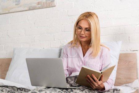 Photo pour Femme dans un pyjama tenant un livre et utilisant un ordinateur portable au lit - image libre de droit