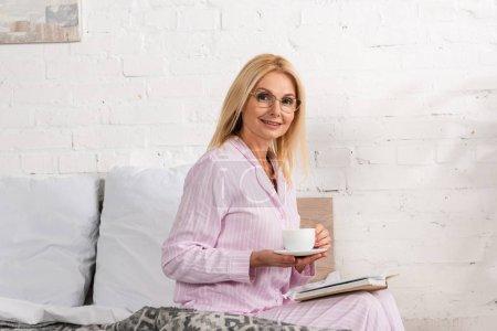 Photo pour Une femme souriante avec un café et un livre assise au lit - image libre de droit