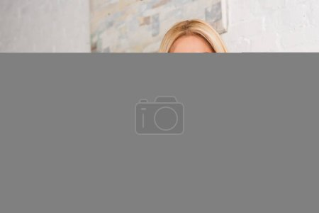 Photo for Blonde woman wearing pajamas and eyeglasses holding coffee cup in bedroom - Royalty Free Image