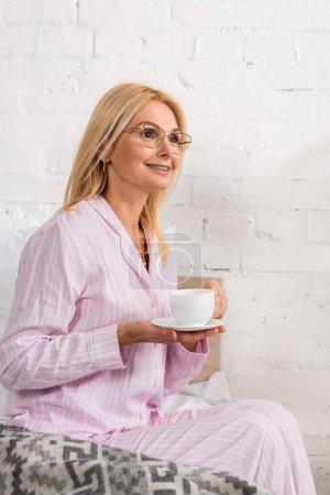 Photo pour Femme souriante dans des pyjamas et des lunettes tenant une tasse de café dans une chambre à coucher - image libre de droit
