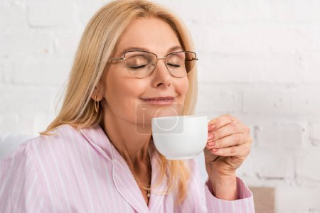 Photo for Smiling woman in eyeglasses smelling coffee in cup at home - Royalty Free Image
