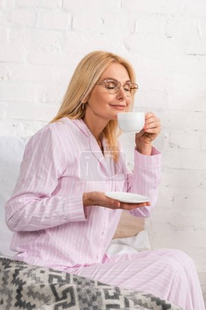 Photo for Smiling woman in pajamas smelling coffee on bed - Royalty Free Image