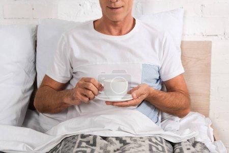 Photo pour Vue recadrée de l'homme tenant une tasse de café au lit - image libre de droit