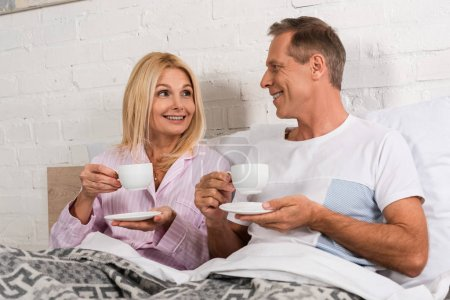 Photo pour Couple souriant buvant du café et se regardant au lit - image libre de droit