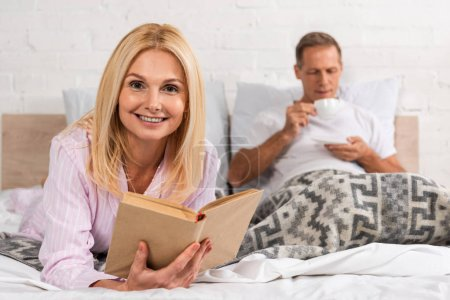 Photo for Smiling woman holding book while husband drinking coffee in bed - Royalty Free Image
