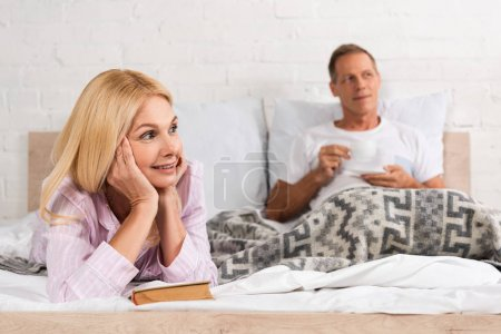 Photo for Smiling woman with book and man drinking coffee in bed - Royalty Free Image