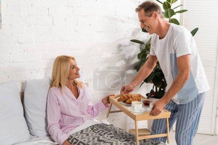Foto de El hombre que da bandeja de desayuno a la mujer sonriente en la cama - Imagen libre de derechos